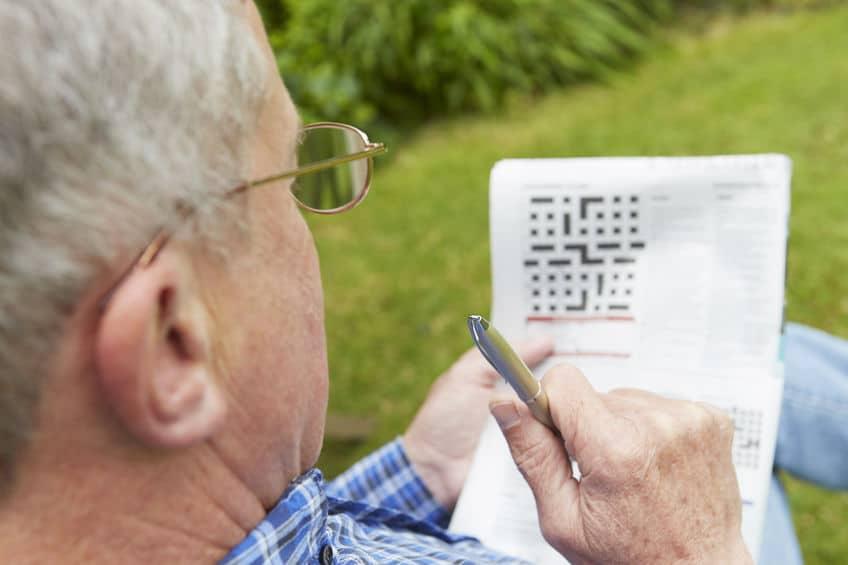 Senior Man Doing Crossword Puzzle In Garden