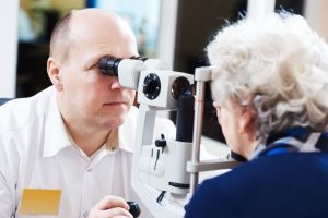 Optometrist examines eyesight of woman