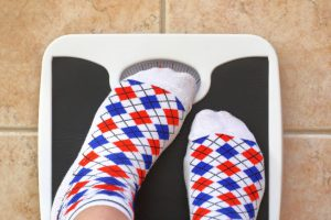 Standing on weighing scales blocking readout with feet.
